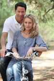 Couple riding bike in forest — Stock Photo