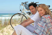 Couple with bikes sitting on the sand dunes — Stock Photo