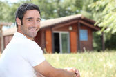Smiling man sitting in front of a cabin — Stock Photo