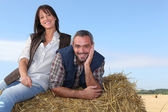 Farming couple sitting on a haystack — Stock Photo