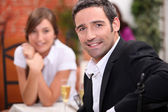 A 40 years old man and a 16 years old girl with sparkling wine on a restaur — Stock Photo