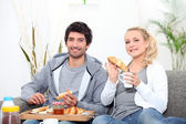 Young couple sharing breakfast in the lounge — Stock Photo