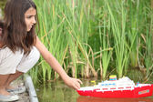 Girl playing with a toy boat on a lake — Stock Photo