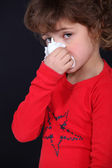 A little girl blowing her noise. — Stock Photo