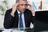 Betonte Kaufmann saß am Schreibtisch — Stockfoto