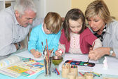 Grandchildren drawing and painting under grandparents' watchful eye — Stockfoto