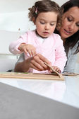 Little girl and nanny making a puzzle — Stock Photo