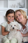 Mother, daughter and white dog sitting in a white living room — Stock Photo