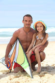 Man on a beach with his daughter and a kite — Stock Photo