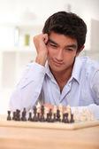 Genç adam bir sonraki satranç hamlesi düşünürken — Stok fotoğraf