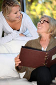 Women looking at a photo album — Stock Photo