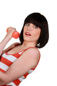 Brunette wearing striped sleeveless top lifting dumbbell — Stock Photo