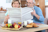 Couple reading newspaper at breakfast — Stock Photo