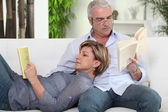Couple reading on their sofa — Foto de Stock