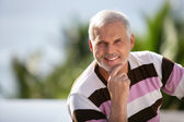 Elderly man sitting in garden — Stock Photo