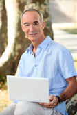 Grey haired man in park with laptop computer — Stock Photo