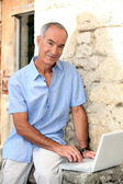 Grey haired man sat by stone wall with laptop — Stock Photo