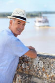 Smiling senior man watching the ferry from Blaye citadel, France — Stock Photo