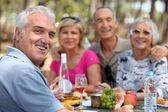 Older couples enjoying an alfresco lunch — Stock Photo