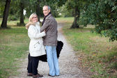 Older couple strolling through a park — Foto de Stock