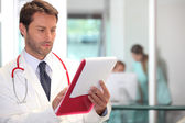 Doctor in hospital reading charts — Foto Stock