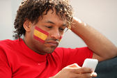 Spanish football supporter with mobile telephone — Stock Photo