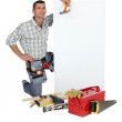 Handyman with a board left blank for your message — Stock Photo #7810730