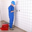 Electrician wiring a large tiled room — Stock Photo