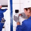 Female electrician installing a continental socket — Stock Photo