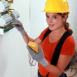 Female electrician taking reading form fuse box — Stock Photo #7811109