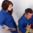 Plumber cutting copper pipe while his female apprentice watches — Stock Photo