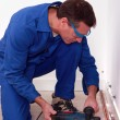 Foto Stock: Plumber using drill to install copper pipes