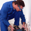 Stock Photo: Plumber using drill to install copper pipes