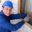 Plumber fixing water supply in bathroom — Stock Photo