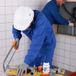 Two plumbers working together is bathroom — Stock Photo #7811267