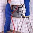 Two plumber fixing bathroom water supply - Stock Photo