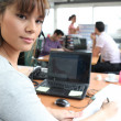 Stock Photo: Woman in a busy office using a laptop and headset