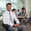 Disabled office worker with colleagues - Stock Photo