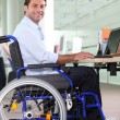 Disabled office worker using a laptop - Stock Photo