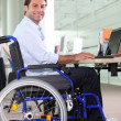 Stock Photo: Disabled office worker using a laptop