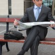 Businessman reading a newspaper on a bench — Stock Photo