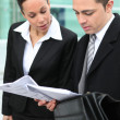 Business couple examining documents outside - Stock Photo