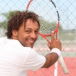 Male tennis player leaning on fence of municipal hard court — Stock Photo #7812029
