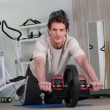 Man using an ab roller (exercise wheel) — Stock Photo
