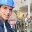 Tradesman standing next to a hoist — Stock Photo
