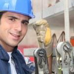 Tradesman standing next to a hoist — Stock Photo