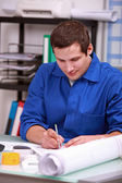 Manual laborer sitting at a desk — Stock Photo