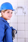 Young woman wearing a blue jumpsuite in front of an electrical schema — Stock Photo