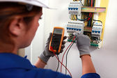 Female electrician checking a fusebox — Photo