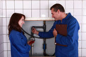 Plumber and his apprentice examining the pipes — Stock Photo